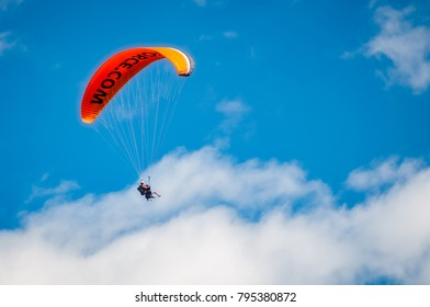 Queenstown Skyline, New Zealand -Decenber 23,2017: A parachute against the blue sky with people having fun practicing tandem paragliding extreme sport.