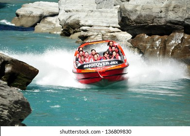 QUEENSTOWN,NZ - FEB 20: Tourists enjoy a high speed jet boat ride on the Shotover River on February 20, 2009 in Queenstown, New Zealand. Queenstown is one of the most popular summer resort in NZ.