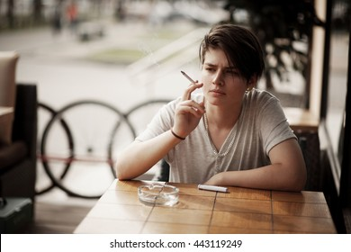 Queer girl sitting in a restaurant and smoking