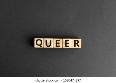 Queer - word from wooden blocks with letters, a gay person unusual or strange queer concept, random letters around, top view gray background