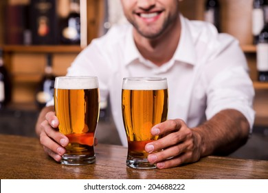 Quench your thirst! Close-up of handsome young male bartender in white shirt stretching out glasses with beer and smiling while standing at the bar counter