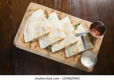 Quesadilla with chicken and sauce on a wooden board