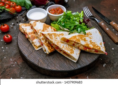 Quesadilla with chicken and sauces on dark board , on dark rustic concrete background