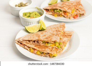 Quesadilla filled with tuna and vegetables served with guacamole and cream sauce on white.