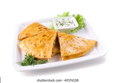 Quesadillas on whte plate with sauce