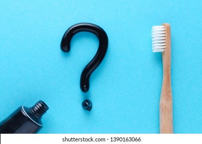 question from black toothpaste, teeth care concept, wooden toothbrush on blue background