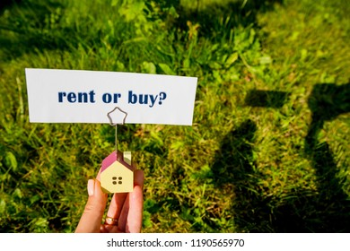 The question to Buy or Rent,typed on a scrap of lined paper and house model in female hand. A decision aided by analysis of the real estate market and our personal finances.Real estate concept.