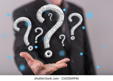 Question concept above the hand of a man in background