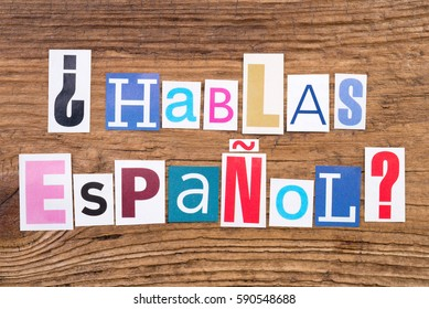 """Question """"Hablas Espanol?"""" in cut out magazine letters on wooden background"""