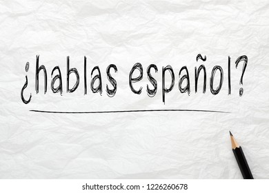 Question Hablas Espanol? Do You Speak Spanish? written with pencil on wrinkled lined paper. Learning languages concept.