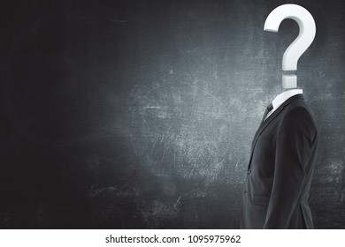 Question headed businessman standing on concrete wall background with copy space. Enquiry concept