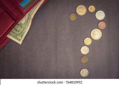 A question made up of coins, a purse with a dollar. Cash settlement, credit payment. Where is the money spent? Top view, vignetting.