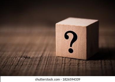 Fragezeichen-Block auf Holzhintergrund mit Kopienraum.