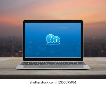 Question mark and information chat icon with modern laptop computer on wooden table over blur of cityscape on warm light sundown, Business customer support online concept