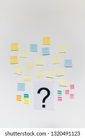 Question mark and multicolored post it on white background.