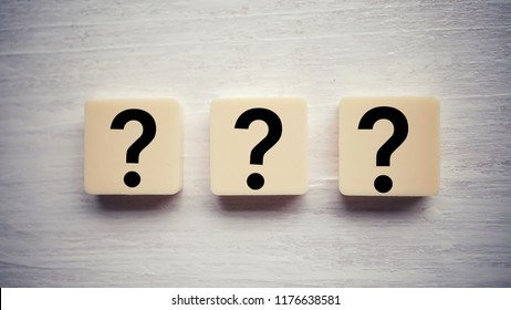 Question mark on alphabet block. Question mark over wooden background