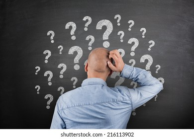 Question Mark on black Blackboard with businessman