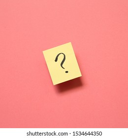 Question mark on memo paper on pink background. Solution concept
