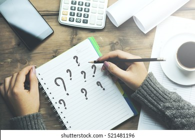 question mark on notebook with woman hand pencil and phone, coffee and calculator on table