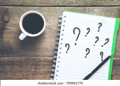 question mark on notepad with coffee cup