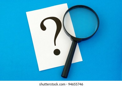 question mark on the paper and a magnifying glass