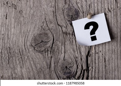 Question mark on a paper pinned with pushpin to a wooden board or tree
