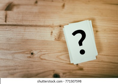 Question mark on wooden desk background. Concept for confusion, question or solution.