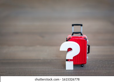 Question mark with Red Luggage Bag on wood table , Problem Concept