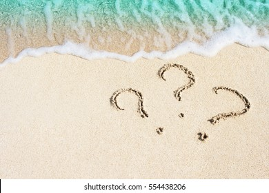 question mark sign handwritten in sand beach