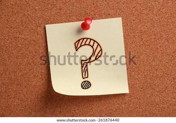 Question mark sign sticky note is pinned on cork.