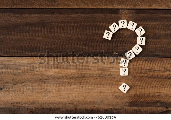question mark tiles arranged forming bigger question mark. question mark on wooden table background