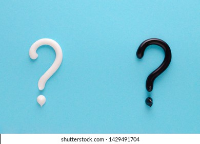 question mark from white and black toothpaste on blue background