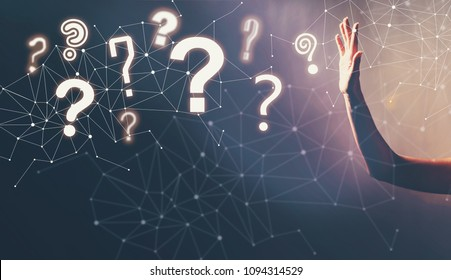 Question Marks with a hand in a dark light background