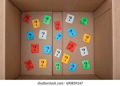 Question marks inside of a cardboard box. Close up.