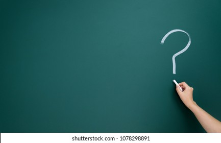 Question marks written on blackboard
