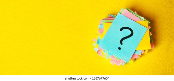 question marks written reminders tickets on yellow vintage paper background.