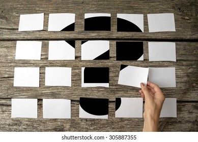 Question or query - solution or answer concept with a woman laying out rows of memo notes with a question mark and placing the last piece in place on the wooden background, close up of her hand.