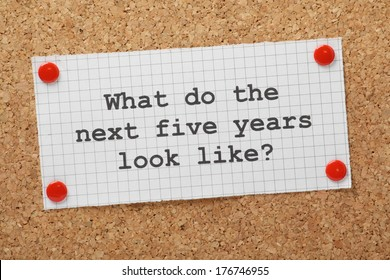The question What Do The Next Five Years Look Like typed on a piece of graph paper and pinned to a cork notice board. A concept for business planning and looking to the future.