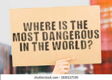 "The question "" Where is the most dangerous in the world? "" on a banner in men's hand with blurred background. Fear. Danger. Insecure. Unsafe. Dangerous"