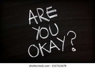 The question Are You Okay written by hand in white chalk on a blackboard