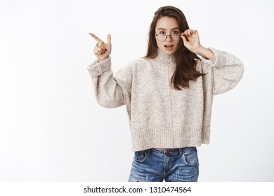Questioned and impressed cute young 20s woman taking off glasses intrigued as pointing at upper left corner being curious with product asking question at camera over gray background