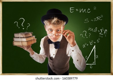 Questioning looking young man with old books near chalkboard