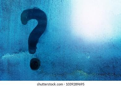 Questionmark written on frosty window, winter iced pattern on frozen window glass,