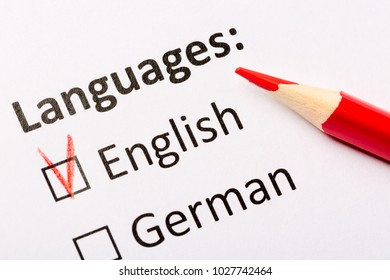 Questionnaire concept. Languages with English and German checkboxes with red pencil. Close up image