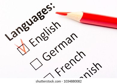Questionnaire concept. Languages with English, German, French, Spanish checkboxes with red pencil. Close up image with focus on the pencil