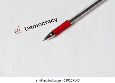 Questionnaire. Red pen and the inscription democracy with check mark on white paper