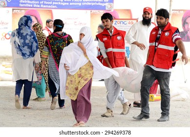 QUETTA, PAKISTAN - JUL 07: Volunteers distribute relief goods among needy people during distribution ceremony ahead of Eid arranged by Pakistan Red Crescent Society on July 07, 2015 in Quetta.