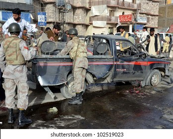 QUETTA, PAKISTAN - MAY 14: Security officials inspect a damaged vehicle, which was destroyed in explosion, at the site of explosion after bomb explosion on May 14, 2012 in Quetta.