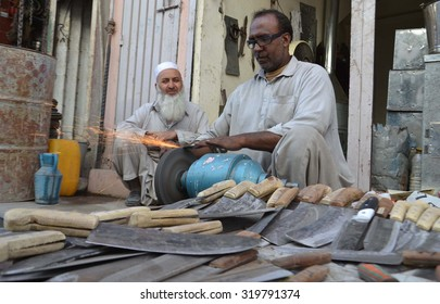 QUETTA, PAKISTAN - SEP 23: Vendor busy in sharpening knives to slaughter animal on the occasion of Eid-ul-Azha coming ahead at Kawari Road on September 23, 2015 in Quetta.