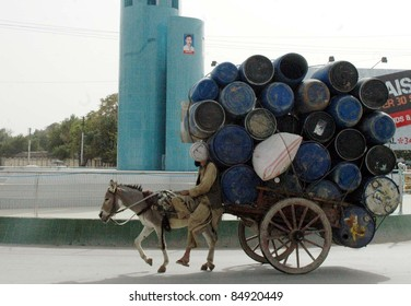 QUETTA, PAKISTAN - SEPT 17: A laborer carries empty drums to earn his livelihood to support this family on his donkey-cart passes through a road on September 17, 2011 in Quetta.